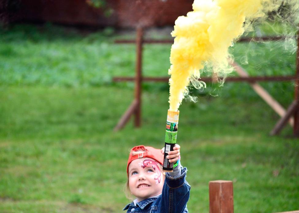 девочка держит цветной дым (факел дымовой ) желтого цвета