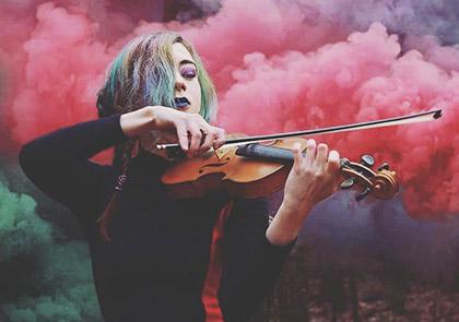 девушка играет на скрипте на фоне цветных дымовых шашек