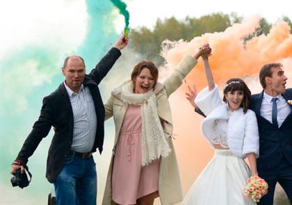 зеленый и оранжевый смок фонтан в руках на свадьбе