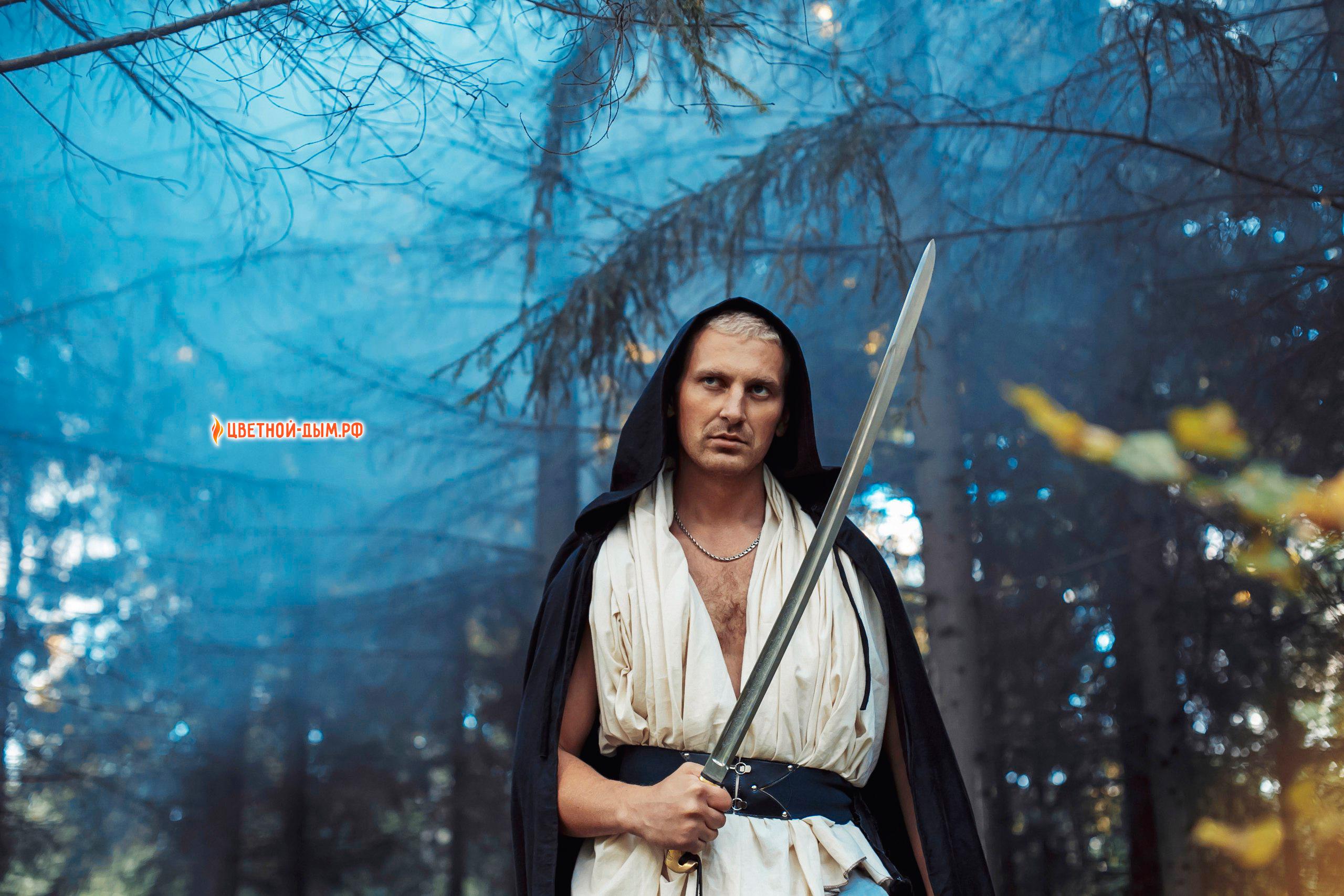 храбрый воин с мечом на фотосессии с цветным дымом