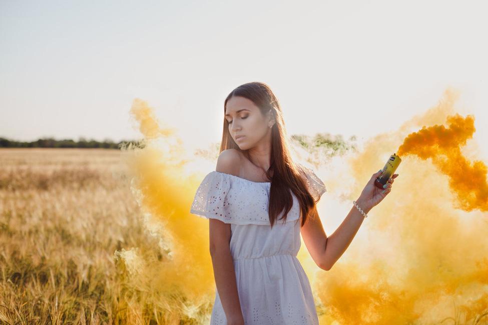 девушка с цветным дымом Smoke Fountain желтый цвет осенью