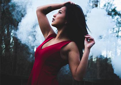 девушка в красном платье с белым дымом как фон